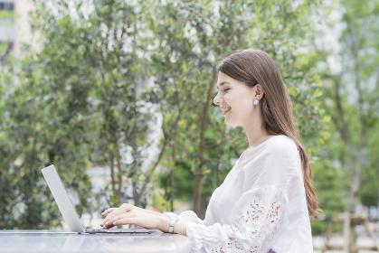 屋外でノートパソコンを操作する女性