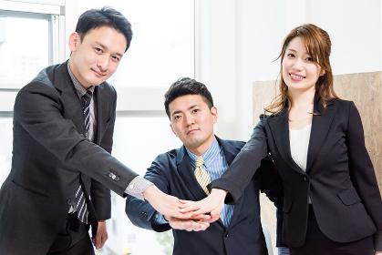 中央で手を合わせる3人のビジネスピープル