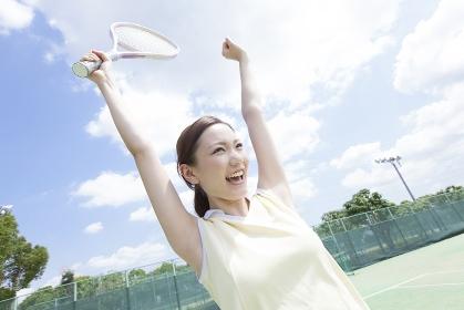 テニスでポイントを決めて喜ぶ女性