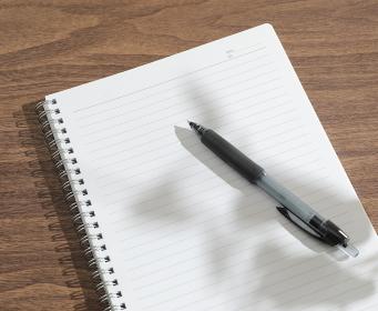 窓辺で開いたノートとペン