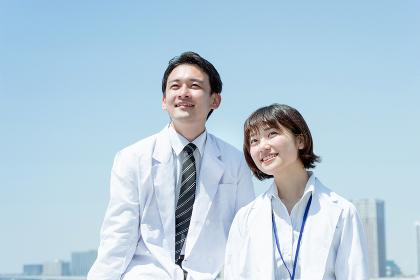 遠くを見つめる白衣の男女(医者と科学者のイメージ)