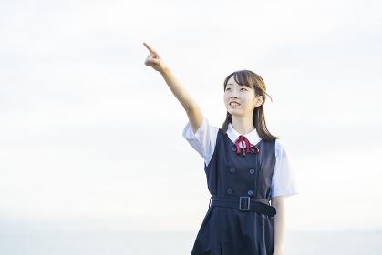 空を指差すアジア人女性の高校生