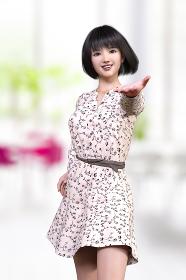 花柄の薄いピンクのシャツワンピースを着た黒髪ボブヘアの笑顔の女の子が片手を前に突き出し提示しているようなポーズ