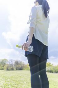 ペットボトルを持ち佇む運動着姿の若い女性