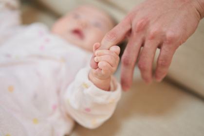 パパの指を握るアジア人の赤ちゃん
