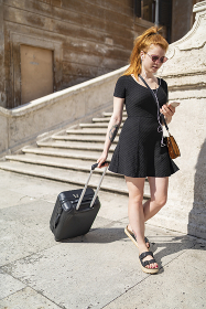 Red hair girl with wired earphones read phone travelling with luggages