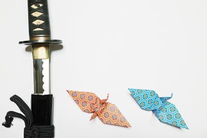 白い紙の左端に配置した抜きかけの日本刀と下に配置した橙色と青色の亀甲花菱柄の折り鶴