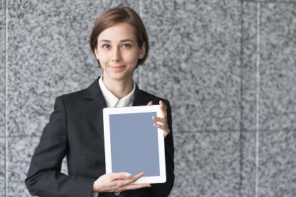 タブレットPCを持つ笑顔の若い女性