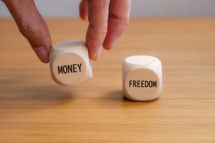 お金のサイコロを持ち上げる手 自由とお金