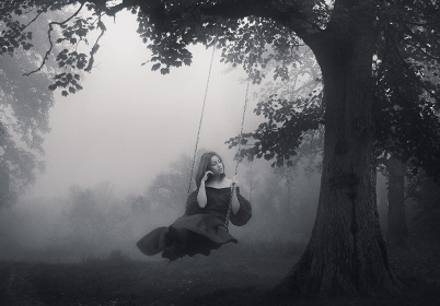 Art portrait of a young lady on a retro swing