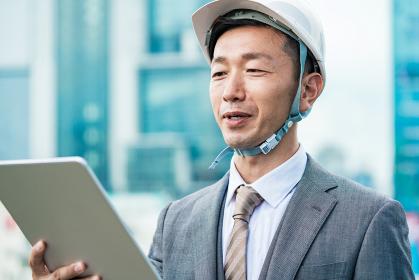 ヘルメットを装着してタブレットPCを見るビジネスマン