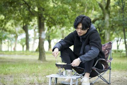 一人キャンプで料理をする若い日本人の男性