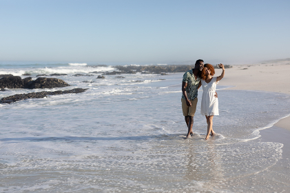 A mixed race couple enjoying free time on beach on a sunny day together, walking, taking photos with a smartphone and holding each other with sun shining on their faces.