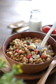 ナチュラルな木の上に置かれた朝食のセットとフルーツグラノーラ