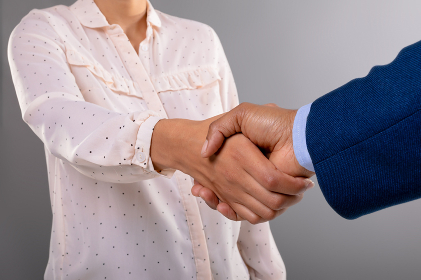 Mid section of businessman and businesswoman shaking hands against grey background. business agreement and professionalism concept