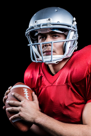 Serious American football player looking away while holding ball
