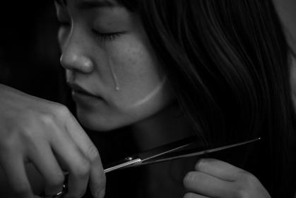 泣きながら髪を切る女性