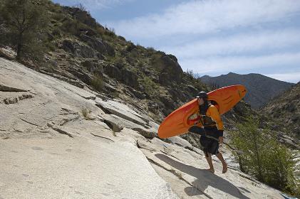 Female Kayaker Walking On Rock