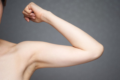 二の腕のたるみを気にする中年の日本人女性