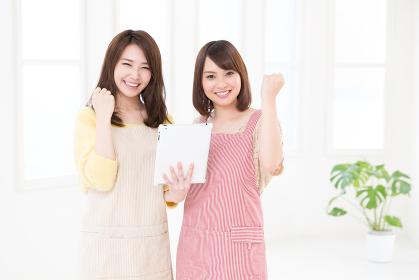 エプロン姿の2人の女性 タブレット