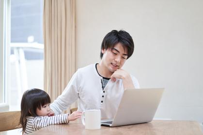 子供に仕事の邪魔をされるアジア人のお父さん