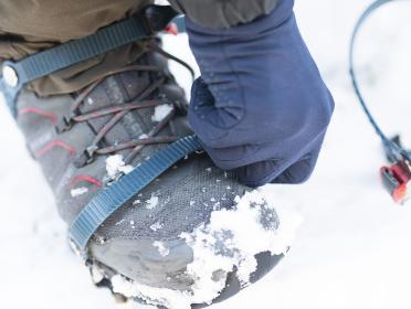 雪山でアイゼンを装着する男性