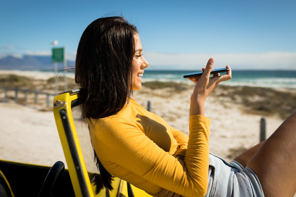 Caucasian woman lying on a beach buggy by the sea talking on smartphone. beach break on summer holiday road trip.