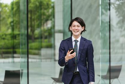出社する若い男性・スマートフォンでIoT・ビジネスイメージ