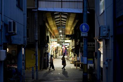 夕方のアーケードの商店街を横切る人影