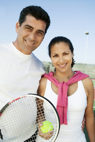 Mixed doubles Tennis Players standing on tennis court portrait