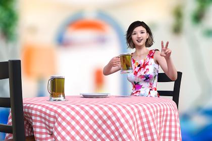 花柄のノースリーブなワンピースを着て赤いギンガムチェック柄のテーブルクロスが敷かれたテーブルに座る女性がビールジョッキを持ってピースサインをしているポーズ