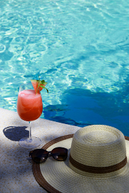 a summer hat, sunglasses and watermelon smoothie cocktail at the pool