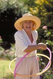 Portrait, Halbfigur, Frau Mitte 60 bekleidet mit heller  Hose,weissem Hemd und Strohhut macht mit 2 Hulahoop Reifen im Garten Gymnastik