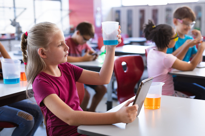 Caucasian boy holding a beaker and digital tablet in science class at laboratory. school and education concept
