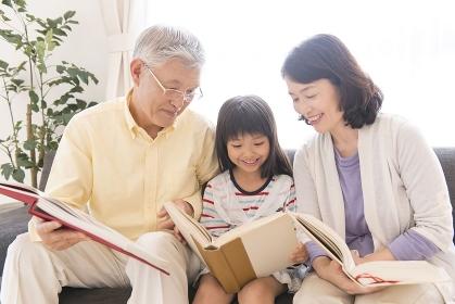 本を読む祖父母と孫