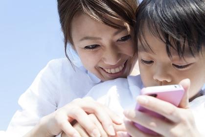 スマートフォンを持つ母子