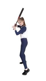 Woman swinging her bat in softball