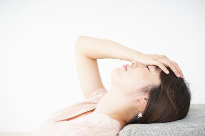 体調不良で横たわる若い女性