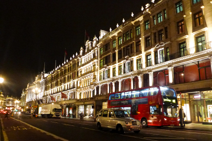 イギリス・ロンドン市街地にてライトアップされた大通りと真っ赤な2階建てバス