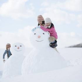 雪だるまと雪遊びをする小学生