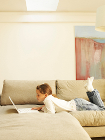 Girl lying on sofa using laptop