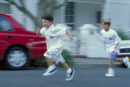 Portrait, Ganzfigur, zwei 7-8 Jahre alte Jungen bekleidet mit weissen T-Shirts und  Shorts laufen an einem roten Auto vorbei die Strasse entlang