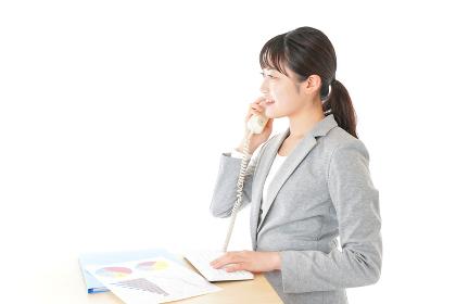 オフィスで固定電話を使う若いビジネスウーマン