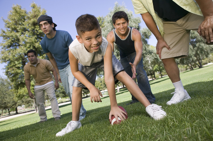Boy Playing American Football With Group Of Men