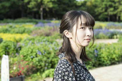 花畑を散歩するアジア人の若い女性