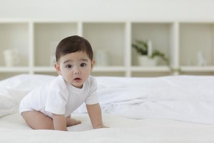 ベッドの上でハイハイをする赤ちゃん