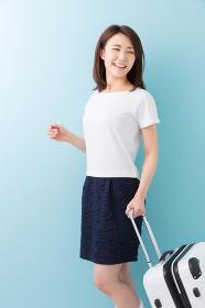 女性とスーツケース 笑顔