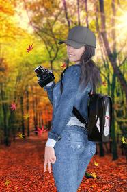 紅葉した森林の中をカメラを持った笑顔の女の子がピースサインをしながら楓が落ちてくる中を歩く
