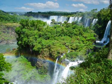 アルゼンチン・ブラジル国境エリアのイグアスの滝にてジャングルの間から流れ落ちる大量の水と虹