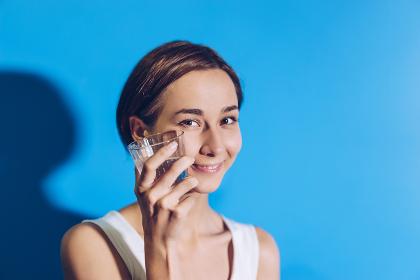 冷たい水を飲む女性(爽やかな青い背景)